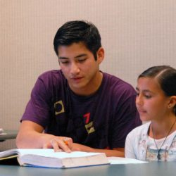 Second Lt. Patrick Leary, 412th Test Support Squadron acquisition manager, helps Vanessa Olmos, a local student, with her mathematics homework. About 20 Edwards company grade officers volunteer their time and effort at the Wanda Kirk Rosamond Library to help children prepare for math tests, homework and make-up work. (Photo by Airman Mike Young)